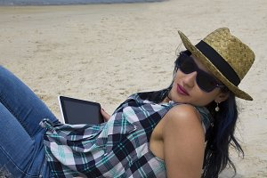 hipster woman on the beach with tablet