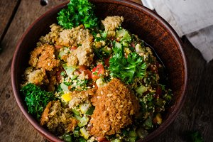 Fresh tabbouleh with falafel - a Middle Eastern salad on wooden background. Selective focus. Toned image. Ramadan food