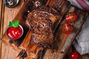 Sliced medium rare grilled Beef steak Ribeye with corn and cherry tomatoes on cutting board on wooden background