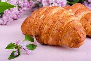 Closeup croissants with lilac flowers on pink slate background. Selective focus
