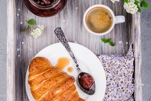 Top view of fresh croissant with strawberry jam and coffee cup  on vintage rustic tray. Breakfast concept.