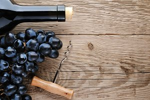 Bottle of wine, corkscrew and grape
