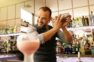 Expert barman is making cocktail .