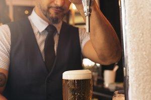 Barman serving beer in a pub.