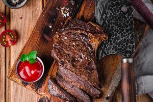 Sliced medium rare grilled Beef steak Ribeye with cherry tomatoes on cutting board on wooden background