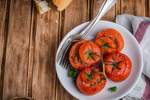 Baked stuffed chicken tomatoes in white bowl on wooden background. Selective focus