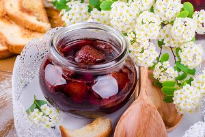 Homemade strawberry jam in jar on white tray on wooden background. Selective focus. Spring mood