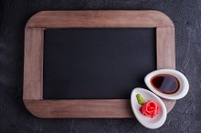 Soy sauce and ginger shape rose on vintage slate chalk board background. Asian style.  Selective focus. Top view