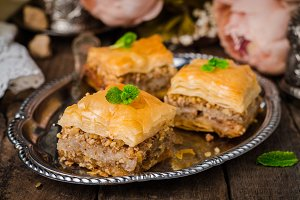 Walnuts baklava in oriental tray on wooden background. East sweets. Ramadan food. Selective focus