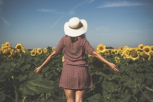 woman in hat looking at sunflower