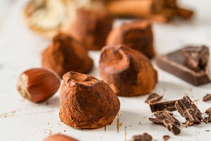 Truffle candies and ingredients on white wood background