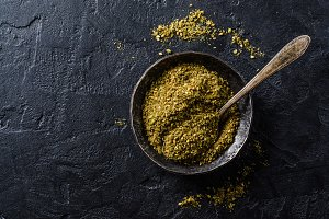Mixed east spice - zaatar or zatar in metal vintage bowl on dark stone background. Selective focus