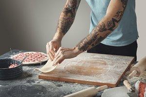 Tattooed man cooks dough