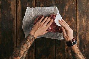 Man cooks meat steaks