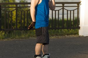 A man riding on roller skates talking on a mobile phone