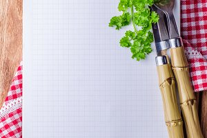 Notebook with parsley, knife and fork on wooden background. Selective focus. Top view. Space for you text
