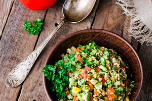 Fresh tabbouleh, a Middle Eastern salad, in clay bowl on wooden background. Selective focus. Toned image