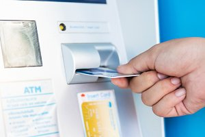 hand inserts credit card into ATM.