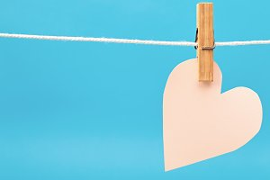 Paper pink heart hanging on twine against blue paper texture for Valentines day