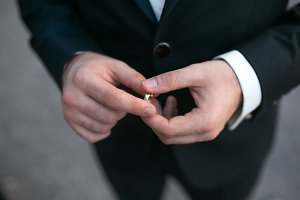groom holding a wedding ring