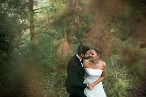 bride and groom dance together in the woods
