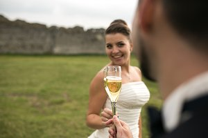 bridal couple clink glasses of champagne