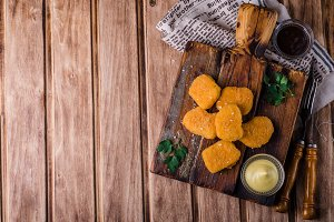 Chicken Nuggets on wooden cutting board with ketchup and sauce, on wooden background. Selective focus. Top view