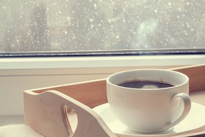Coffee on tray and sweater in from of snowing winter