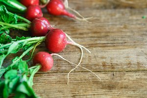 large bunch of fresh radish on rustic wooden boards