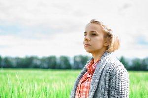 Portrait of beautiful girl in green field