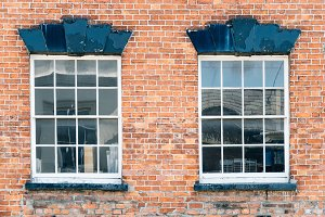 Two windows on a brick wall