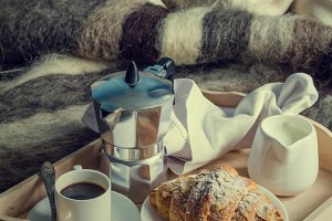 Breakfast in bed - coffee, croissant, milk on tray