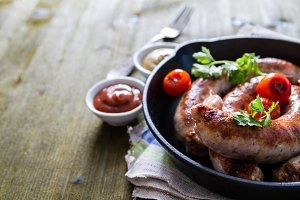 Grilled sausages on pan with herbs and spices