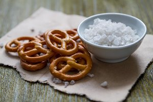 Pretzels with salt on wood background