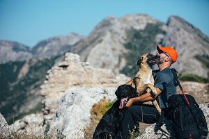Mountaineer hugging with pet dog