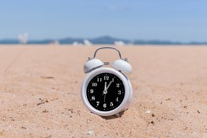 analog clocks in sand on beach
