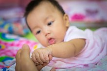 baby hand holding mother's finger