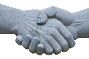 stone sculpture of shaking hands