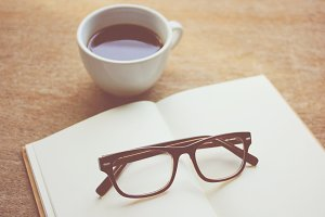 Eyeglasses on notebook and coffee