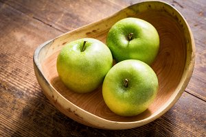 Green apples in wooden bowl