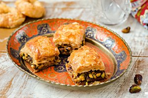 Baklava with pistachios in vintage iron bowl on wooden background