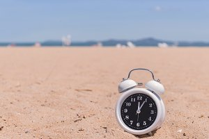 analog clocks in sand on the beach