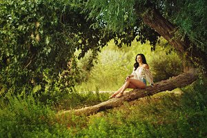 Boho Girl sitting on fallen tree