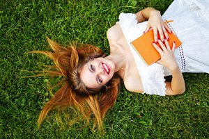 Girl with the book lying on lawn.
