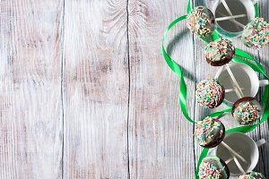 Colorful chocolate cake pops on wooden background