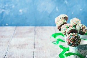 Colorful birthday chocolate cake pops on wooden background