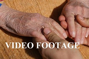 Male hands comforting elderly hands