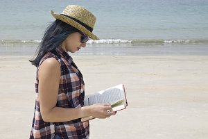 young woman with book on the beach