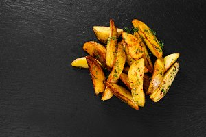 Potato wedges on black background