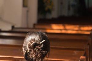 One woman sitting in church.